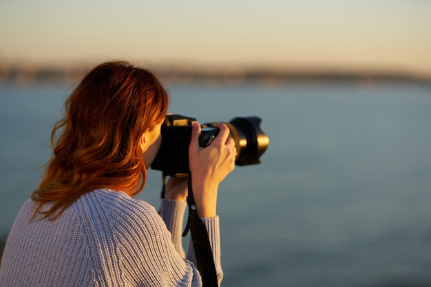 Woman with professional camera at sunset by the sea