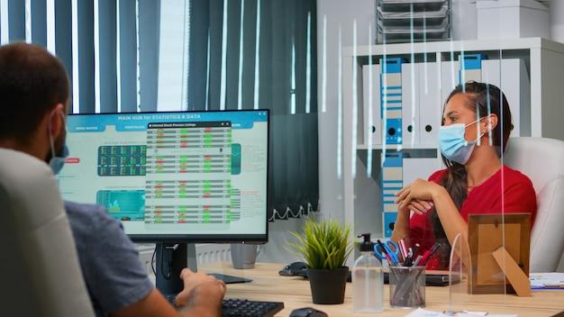現代の新しい通常のオフィスでオンライン会議会議を持っている保護マスクを持つ女性。インターネット技術を使用した仮想ウェビナー中にリモートチームとチャットする職場で働くフリーランサー