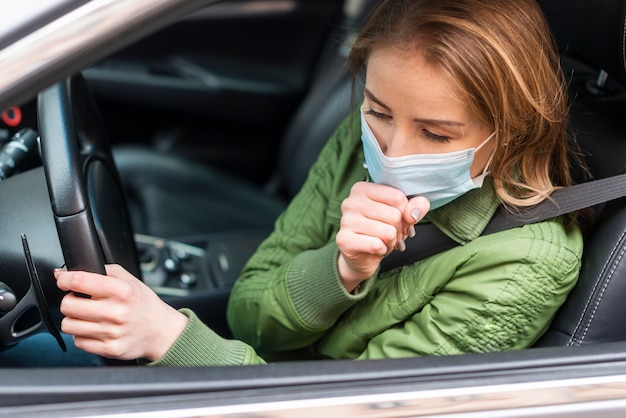 Woman with protection mask in her car coughing