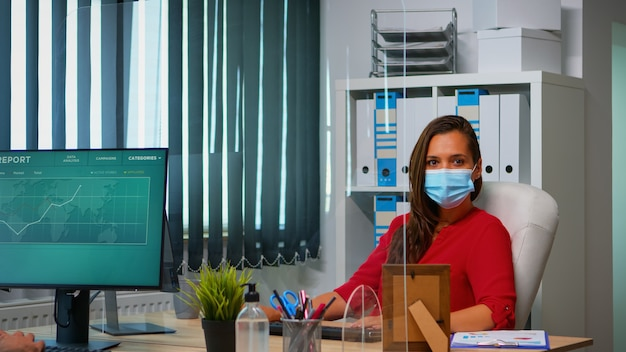 Woman with protection mask working and looking at camera sitting in front of pc. employees in workspace in corporate company typing on computer keyboard looking at desktop respecting social distancing