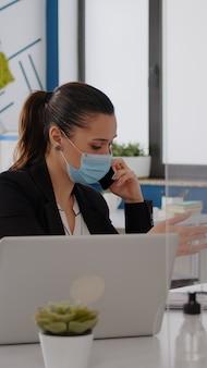 Женщина с защитной маской работает на портативном компьютере в офисе компании