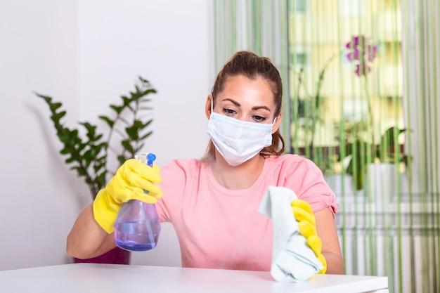 保護手袋と消毒剤をふりかけ、テーブルを掃除する顔のマスクを持つ女性。おげんきで。