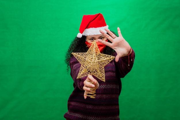 保護マスクとサンタの帽子を持つ女性は彼女の手でクリスマスの黄金の星を保持します