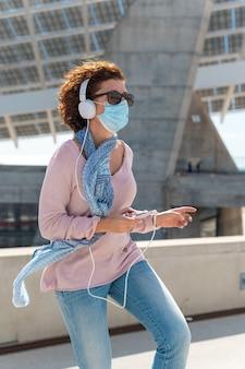 Женщина с защитной маской и солнцезащитными очками слушает музыку и танцует