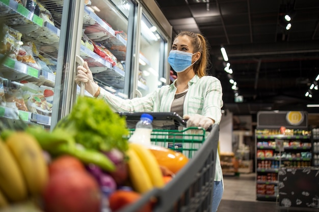 Woman with protective mask and gloves shopping in supermarket during covid-19 pandemic or corona virus