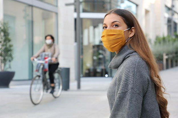 Woman with protective mask looks around sitting on bench waiting for better times in modern city