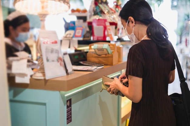 Woman with protective mask paying bill at cashier counter in restaurant.