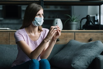 Woman with protective mask sitting on sofa holding syringe