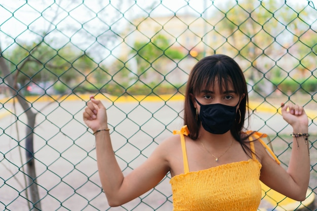 Woman with protective mask in the street leaning on a wire mesh