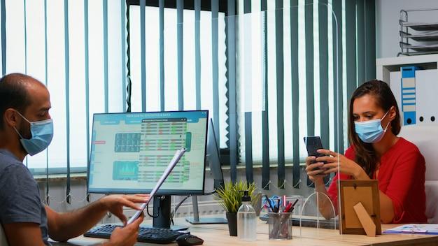 Donna con maschera protettiva che digita sul telefono mentre il collega lavora utilizzando gli appunti rispettando il distanziamento sociale. libero professionista nel nuovo ufficio normale che chatta scrivendo sul cellulare con la tecnologia internet