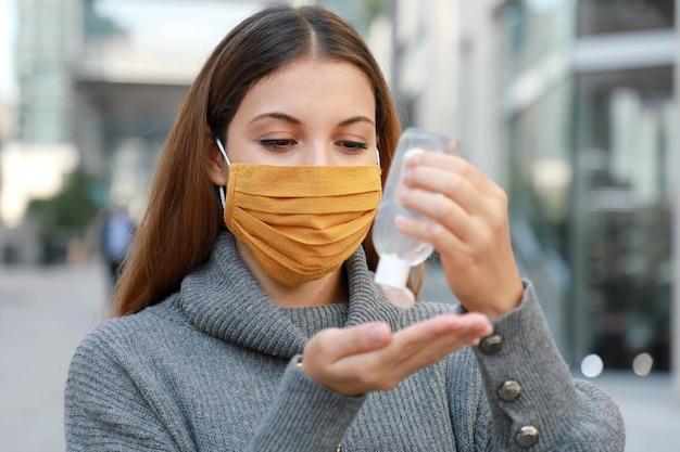 현대 도시 거리에서 알코올 젤 소독제 손을 사용하여 보호 마스크를 가진 여자
