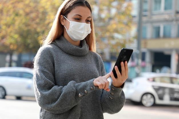 街の通りを歩く携帯電話を使用して保護マスクを持つ女性