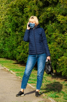 Woman with protective mask using smart phone in park, coronavirus concept