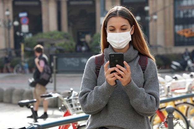 スマートフォンを使用して、市内中心部のディスプレイを見ている保護マスクを持つ女性