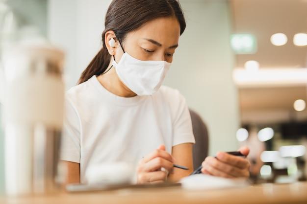 Женщина с защитной маской работает на смартфоне с беспроводными наушниками в кафе.