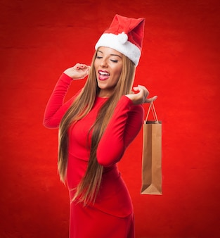 Woman with a purchase bag with a santa's hat