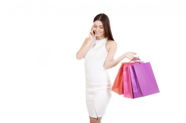 Donna con i sacchetti di acquisto che comunica sul suo cellulare