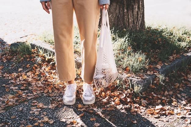 제로 웨이스트 샵의 상점가 배경에서 재사용 가능한 면봉투를 구매한 여성