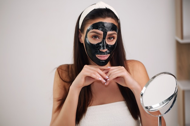 Woman with purifying peel-off black mask