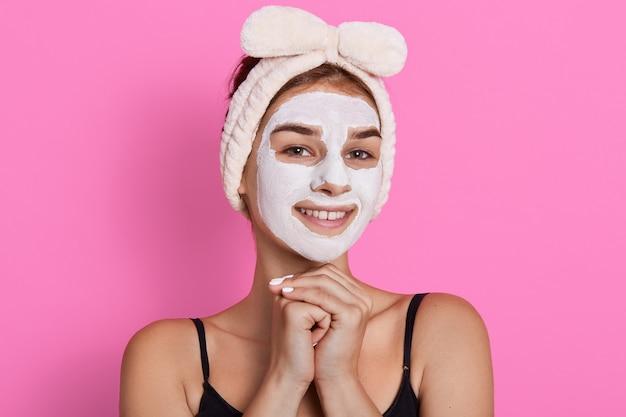 彼女の顔に白いマスクを浄化する女性