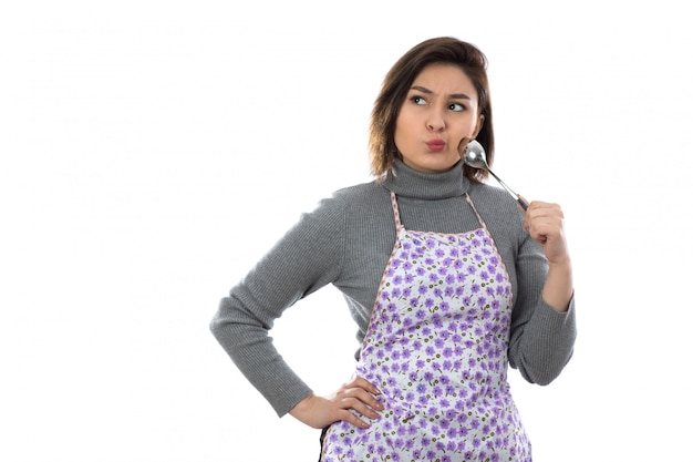 Woman with purple apron and holding a spoon
