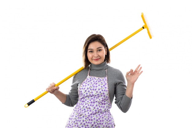 Woman with purple apron and a mop