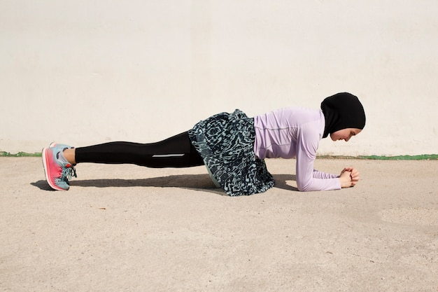 Woman with purple jacket doing planks