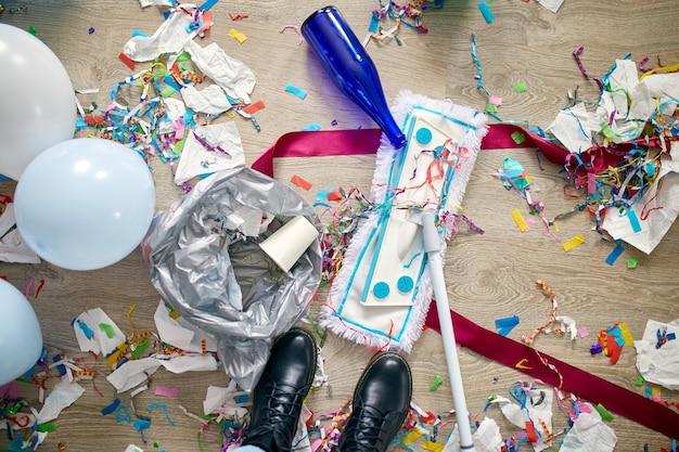 パーティーの紙吹雪の後に部屋の床の混乱を掃除するプッシュブルームを持つ女性