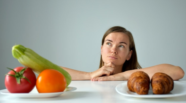 Woman with puzzled sight in choosing between vegetables and dessert.