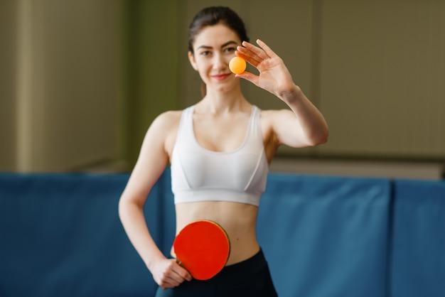 ラケットを持つ女性は、屋内でピンポンボールを示しています。