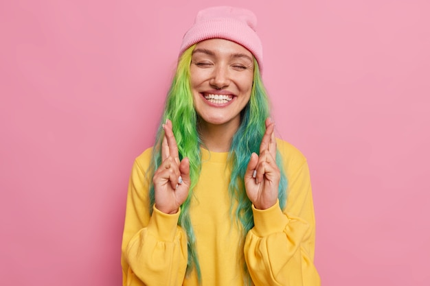 虹のヘアスタイルを持つ女性は目を閉じて指を交差させます幸運の笑顔を信じて気持ちよく素晴らしい結果を期待していますピンクの壁に隔離された帽子とジャンパーを着ています