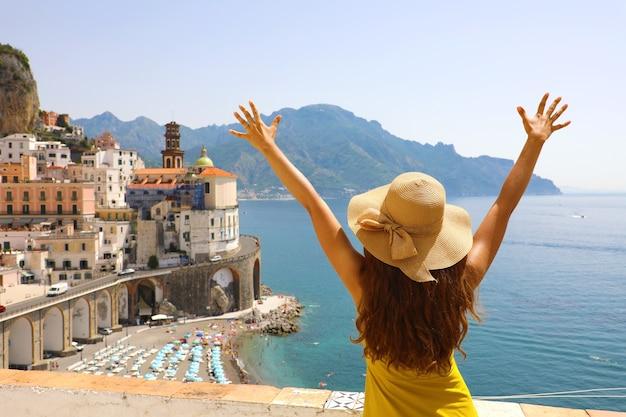 イタリアのアマルフィ海岸、アトラーニ村を見ている腕を上げた女性