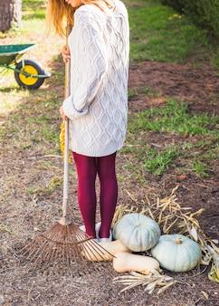 Woman with rake near vegetables
