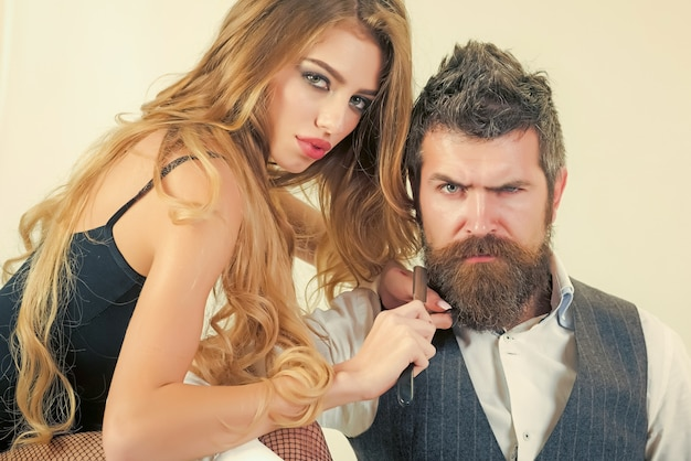 Woman with razor, scissors cut hair of man