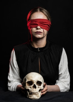 Woman with red blindfold holding skull