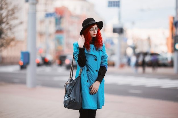 Woman with red curly hair in blue coat and black round glasses on  of big city.