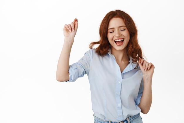 붉은 곱슬머리를 한 여자, 여가 시간에 즐겁게 놀고, 근심없고 행복한 미소를 짓고, 여가를 즐기고, 흰색 블라우스에 서 있는