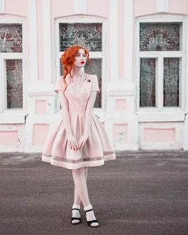 A woman with red curly hair in a peach dress on  vintage window. red-haired girl with pale skin, blue eyes, a bright unusual appearance and red lips