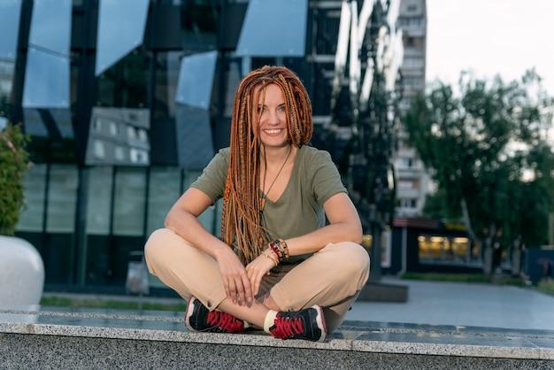 Женщина с красными дредами в позе лотоса сидит на сером парапете и улыбается. веселая девочка. офисное здание на фоне