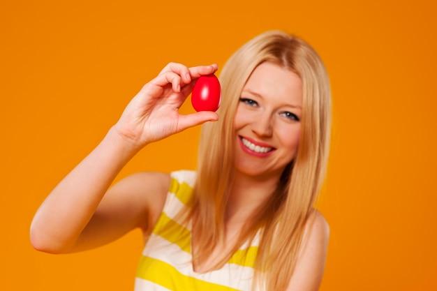 赤いイースターエッグを持つ女性