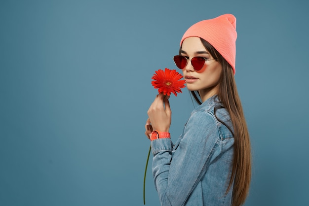 Woman with red flower in hands pink hat fashionable clothes glamor