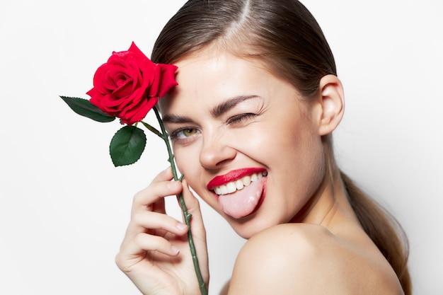 Женщина с красным цветком показывает язык, прищурив один глаз роскошный светлый фон