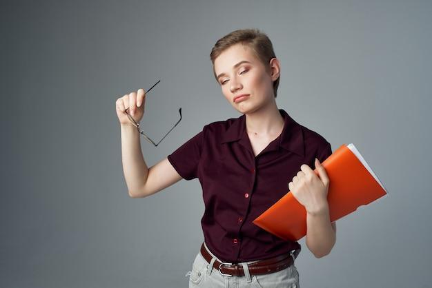 手学生教育スタジオで赤いフォルダを持つ女性