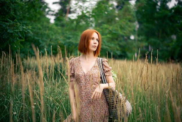 夏の野原で40歳の赤い髪の女性