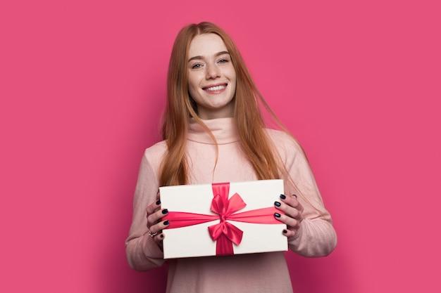 빨간 머리와 주근깨를 가진 여자는 카메라 선물 상자에 잘 포장 포즈와 빨간 벽에 미소를 보여줍니다