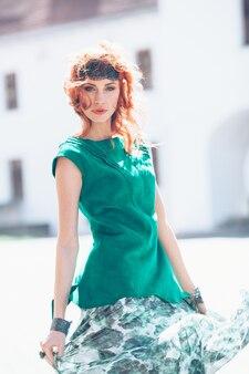 Женщина с рыжими волосами и зеленым платьем
