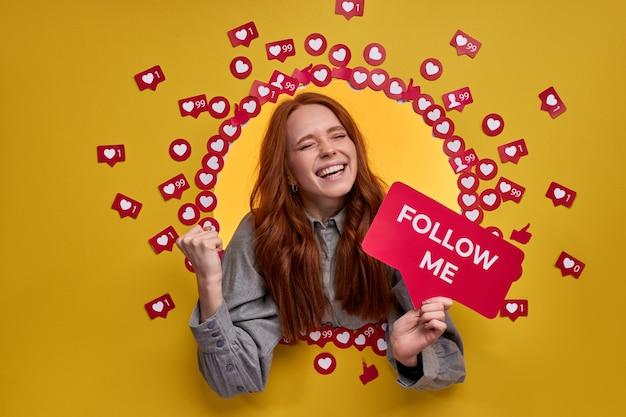 빨간 머리를 가진 여자는 노란색 벽에 인터넷에서 블로그를 따르도록 요청
