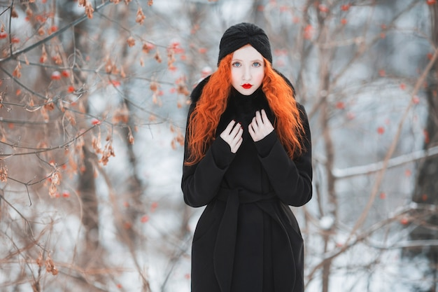 A woman with red hair in a black coat with fur on a  of winter forest.