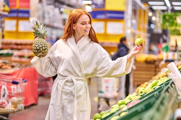 Женщина с рыжими волосами покупает свежие овощи и фрукты в супермаркете, стоит в халате, наслаждается покупками и сравнивает продукты питания