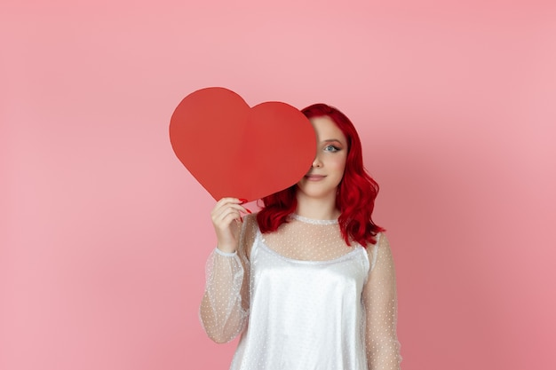Woman with red hair hides half of her face behind a large paper red heart